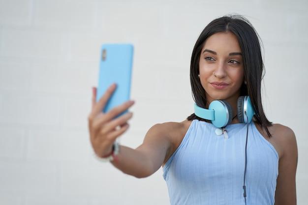 La belle femme prend un selfie avec le smartphone avec les écouteurs sur son cou