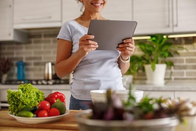 Belle femme prépare de délicieux plats dans sa cuisine à domicile