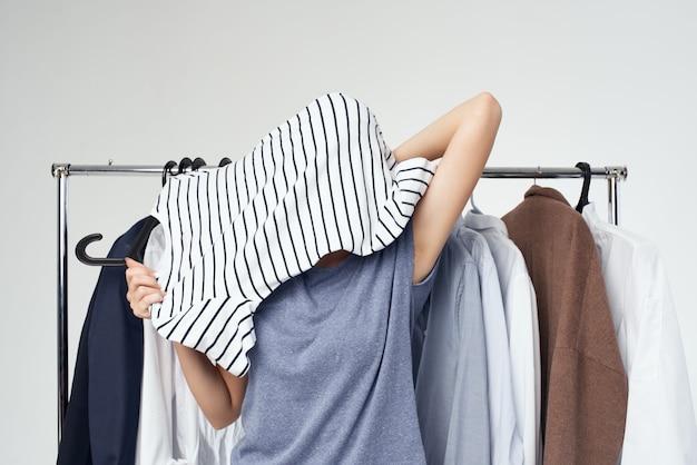 Belle femme près de fond clair accro du shopping de vêtements