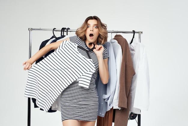 Belle femme près de vêtements accro du shopping fond isolé
