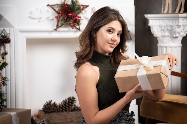 Belle femme présente dans la main assise posant pour la caméra