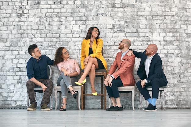 Belle femme professionnelle joyeuse portant des lunettes assis avec des collègues masculins et chef d'équipe dans la salle de conférence au travail