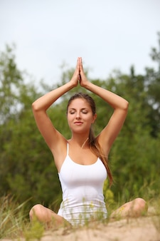 Belle femme profiter du yoga à la forêt