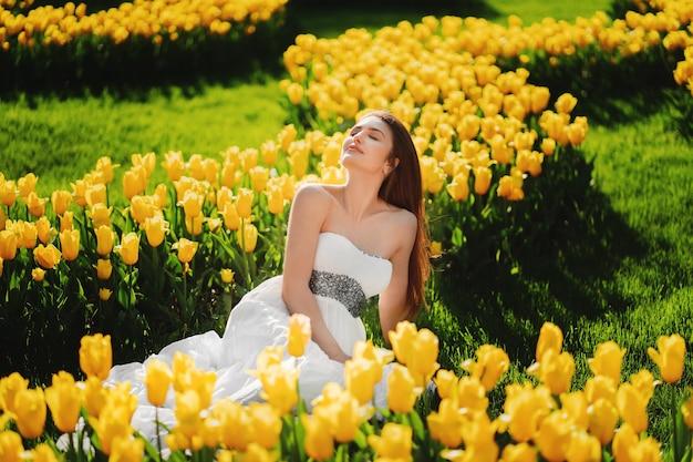 Belle femme en promenade sur le champ de tulipes en fleurs
