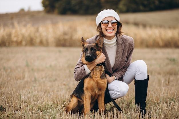 Belle femme promenant son chien dans un champ