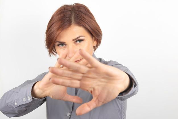 Belle femme proteste avec l'aide de ses mains sa protestation et ses émotions de déni