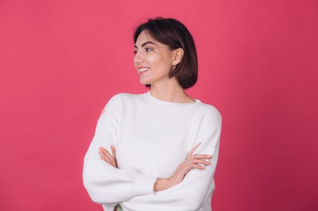 Belle femme en pull blanc décontracté sur mur rouge