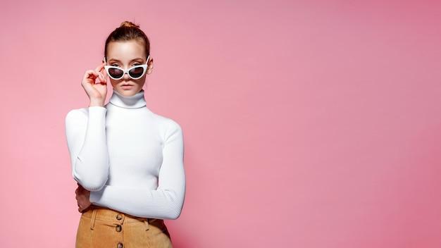 Belle femme avec un pull blanc posant