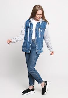 Belle femme en pull en denim et jeans sur fond blanc. concept photo pour la publicité de jeans. beau mannequin.