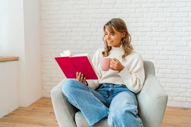 Belle femme en pull doux et chaud profitant d'une tasse de thé et d'un livre de lecture dans un agréable matin d'hiver