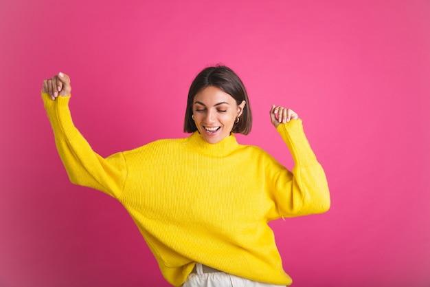 Belle femme en pull jaune vif isolé sur rose heureux sourire en mouvement danse excitée