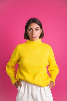 Belle femme en pull jaune vif isolée sur un regard rose à l'avant avec un visage triste et déçu