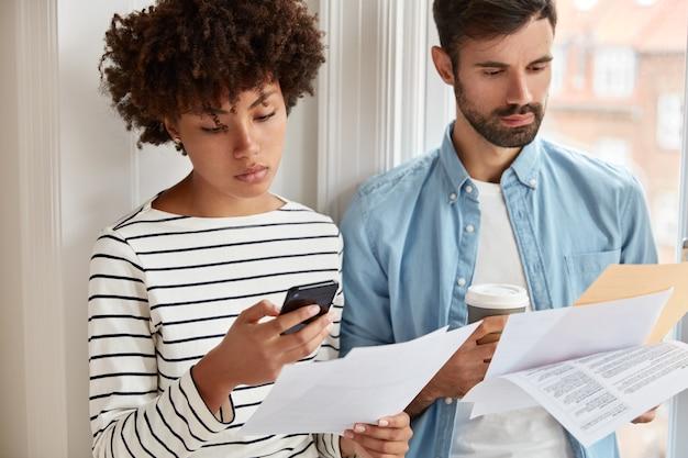 Belle femme en pull rayé rend la comptabilité sur téléphone portable, vérifie les chiffres au document