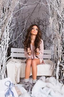 Belle femme en pull rose tendre avec un corps parfait, assise sur une terrasse décorée de lumière.
