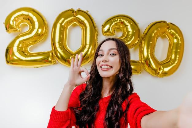 Belle femme en pull rouge faisant selfie drôle devant des ballons de nouvel an 2020