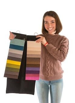 Belle femme en pull tenant des échantillons de tissu isolés sur blanc