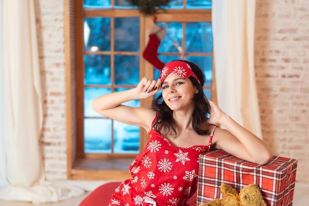 Belle femme en pyjama avec boîte-cadeau
