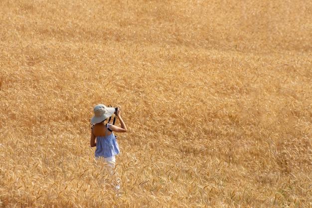 Belle femme qui aime prendre des photos dans les champs d'orge