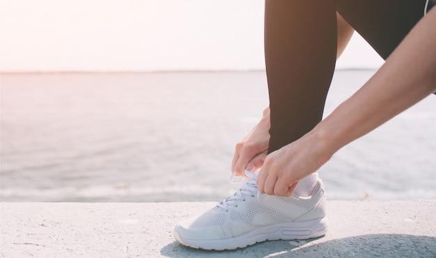Belle femme qui court pendant le coucher du soleil. jeune modèle de fitness près de bord de mer. vêtu de vêtements de sport. baskets cordes