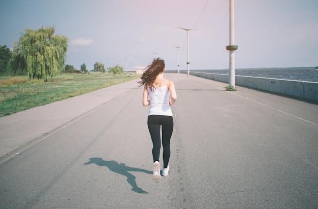 Belle femme qui court pendant le coucher du soleil. jeune modèle de fitness près de bord de mer. vêtu de vêtements de sport.