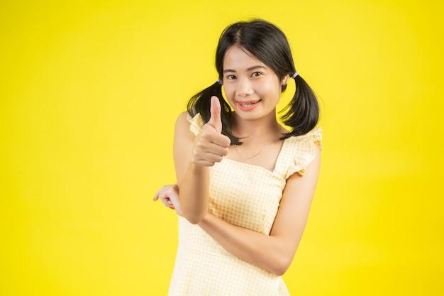 Une belle femme qui est heureuse en montrant divers gestes sur un jaune.