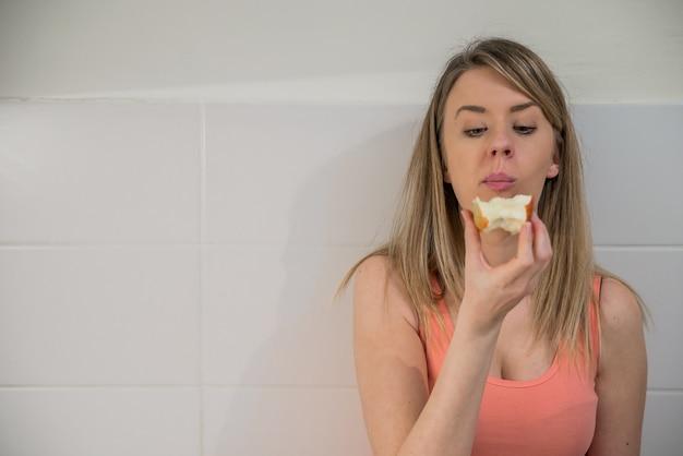 Belle femme qui mange sainement et souriante. une jeune femme charmante maquilleuse aux cheveux longs féminins détient de gros fruits aux pommes rouges. une alimentation saine, une alimentation végétarienne, un régime et un concept de personne.