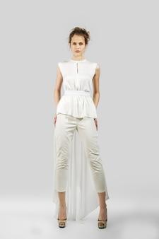 Belle femme qui pose en pantalon et chemisier. portrait en pied du mannequin.