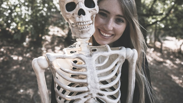 Belle femme qui rit derrière le squelette