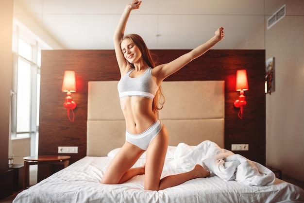Belle femme qui s'étend dans son lit, se réveille. étirement du matin dans la chambre