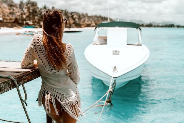 Belle femme de race blanche aux longs cheveux bruns en robe d'été profitant de la vue.