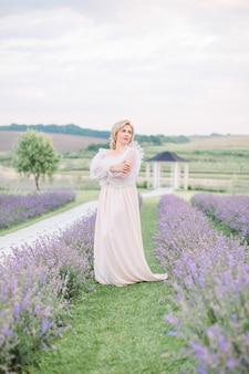 Belle femme de race blanche blonde d'âge moyen dans un champ de lavande. une femme en longue robe blanche élégante marche sur le champ de lavande.