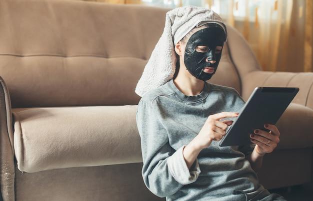 Belle femme de race blanche avec un masque en papier noir sur le visage à l'aide d'une tablette assis sur le sol près du canapé