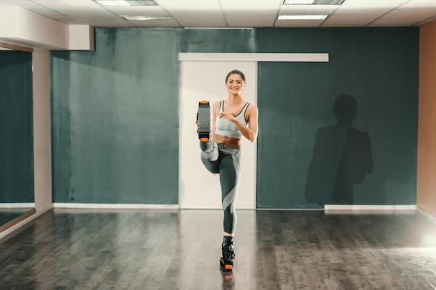Belle femme de race blanche mince en tenue de sport debout sur une jambe tout en portant des chaussures de sauts kangoo.