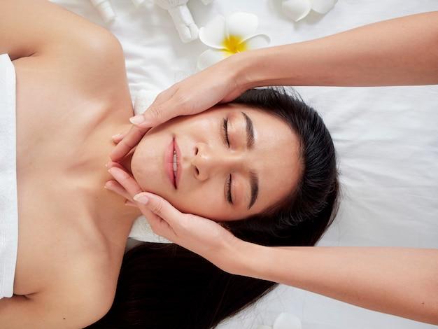 Belle femme recevant un massage facial dans le spa.