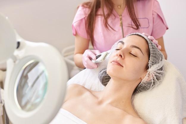 Belle femme recevant un peeling facial aux ultrasons. procédure de nettoyage de la peau au salon de beauté spa.