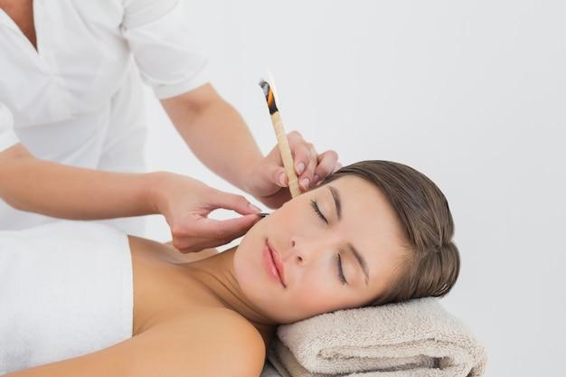 Belle femme recevant un traitement de bougie d'oreille au centre de spa