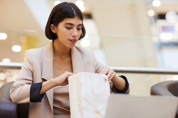 Belle femme à la recherche de sac à provisions