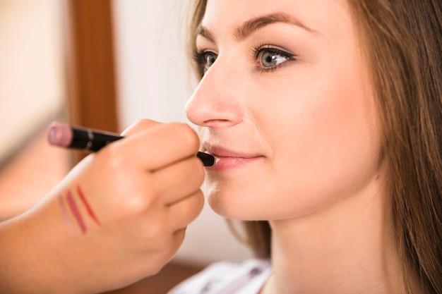 Belle femme reçoit le maquillage de l'artiste