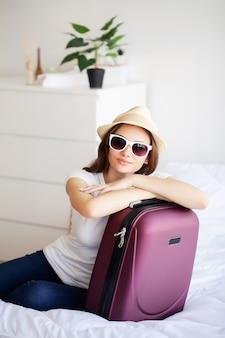 Belle femme recueille des vêtements dans une valise de voyage lors d'un voyage