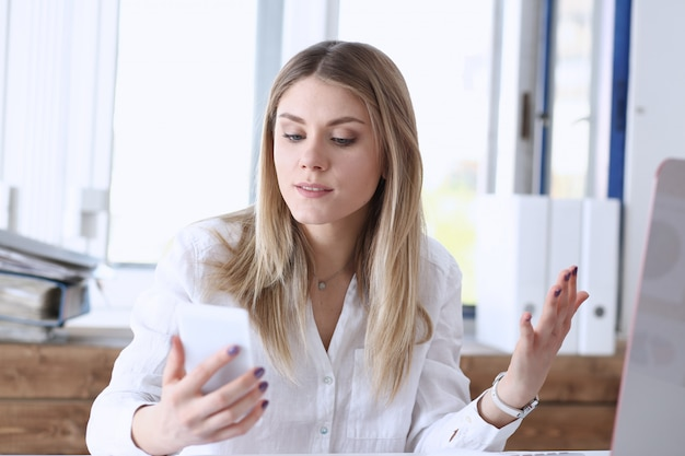 Belle femme réfléchie blonde regarde téléphone portable en portrait de la main.