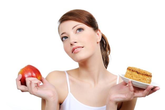 Belle femme réfléchie avec de la nourriture dans ses mains