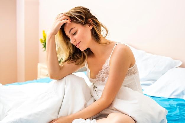 Belle femme regardant au lit