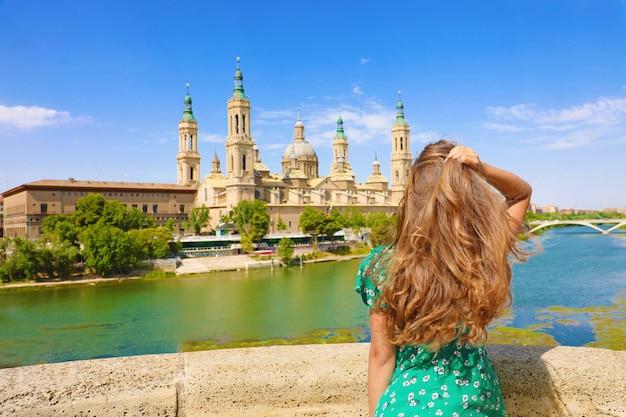 Belle femme regardant la basilique cathédrale de notre-dame du pilier à saragosse, espagne