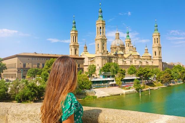 Belle femme regardant la basilique cathédrale de saragosse de notre-dame du pilier, saragosse, espagne