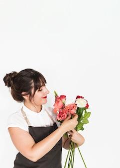 Belle femme regardant un bouquet de fleurs sur fond blanc