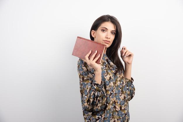 Belle femme regardant la caméra avec livre.