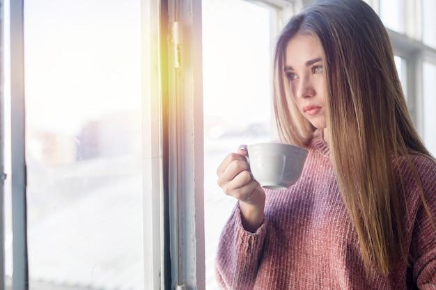 Belle femme regardant par la fenêtre, tenant une tasse de thé