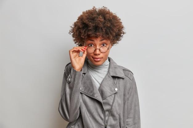 Belle femme regarde étonnamment à travers des lunettes vêtues d'une veste grise élégante se demande quelque chose entend des poses de révélation inattendues à l'intérieur