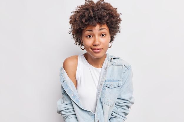 Une belle femme regarde avec une expression confuse montre que l'épaule nue enlève la veste en jean a une expression hésitante ne sait pas quoi faire isolé sur un mur blanc
