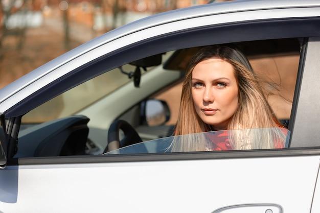 Belle femme regarde hors d'une voiture au volant